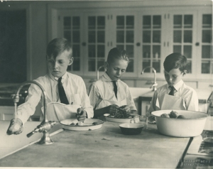 Three young boys prepare food during a child nutrition class hosted by the College of Human Ecology in 1925